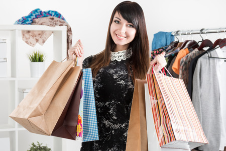 woman closet: Young beautiful smiling woman holding paper bags with purchases. Sale and shopping concept