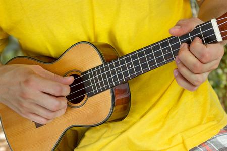 acoustical: Mans hands playing ukulele