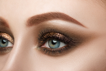 eyeshadow: Close-up view of female blue eye with beautiful make-up. Perfect Make-up closeup.