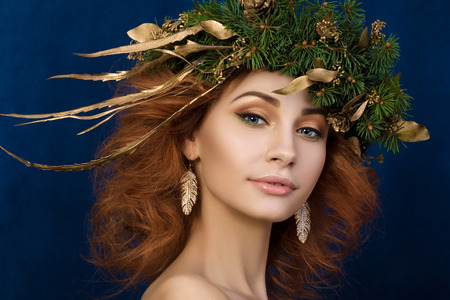 firry: Portrait of young beautiful redhaired woman with firry wreath with golden leaves in her hair.