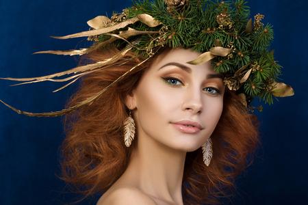 pluma: Retrato de mujer hermosa joven pelirroja con la guirnalda firry con hojas de oro en el pelo.
