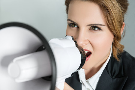 loud speaker: Closeup portrait of young business woman shouting with a megaphone