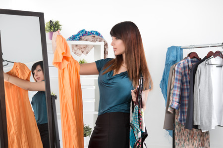 Beautiful young woman standing between mirror and rack with clothes making chioce