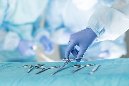 quir�rgico: Primer plano de la enfermera instrumentista teniendo instrumentos m�dicos para el funcionamiento con colegas realizando en segundo plano
