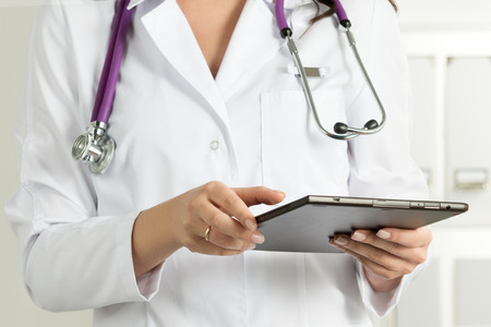 Female Doctor Holding Tablet PC. Doctors hands close-up. Medical service and health care concept.