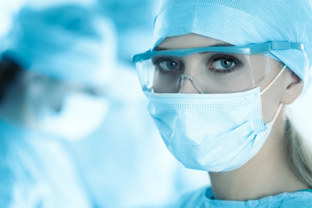 surgeon mask: Close-up of surgeon woman looking at camera with colleagues performing in background in operation room. Toned in blue Stock Photo
