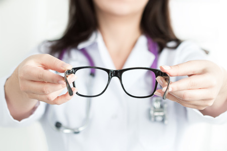 Female oculist doctors hands giving a pair of black glasses. Good vision concept Stockfoto