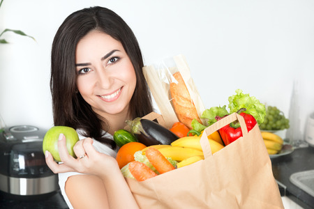 canastas con frutas: Retrato de mujer joven y bella morena de pie en su cocina con la bolsa de papel grande simplemente entregado lleno de comida vegetariana y que sostiene la manzana verde
