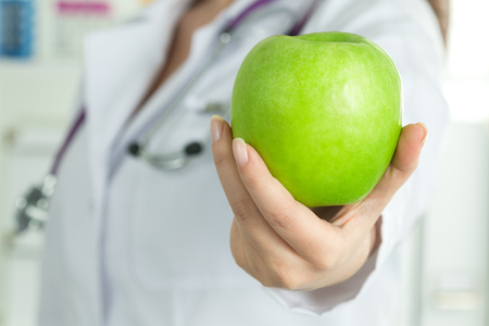 Female doctors hand giving fresh green apple. Healthy life, wholesome and healthcare concept. Copy space
