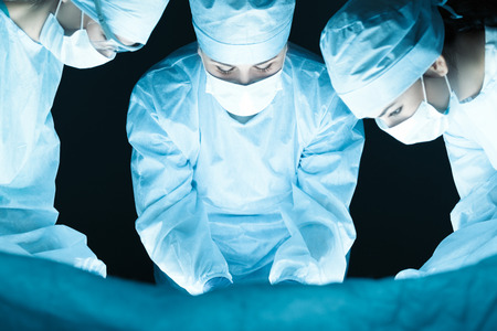 operation theatre: Medical team performing operation. Group of surgeon at work in operating theatre tonned in blue