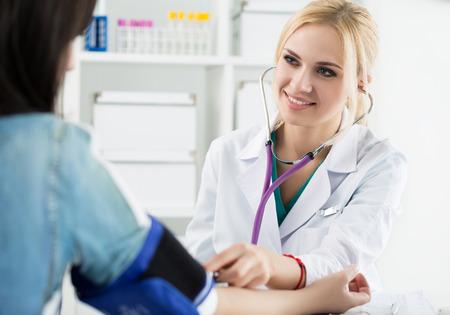 美しい笑みを浮かべて陽気な女性医学の医者の患者に血圧を測定します。メディカル ・ ヘルスケアの概念