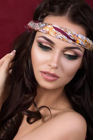 ojos marrones: Retrato de la hermosa mujer morena con la moda de maquillaje y colorido pañuelo en la cabeza Foto de archivo