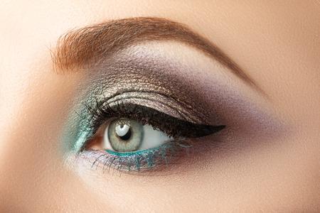 Primer plano del ojo de la mujer con maquillaje moderno creativo. Ojos ahumados y flecha.