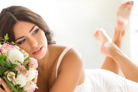 Beautiful bride in white lingerie holding nuptial bouquet Stock Photo