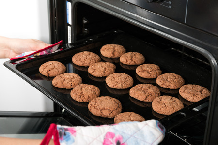 Woman getting roasting pan with oat cookies out of oven