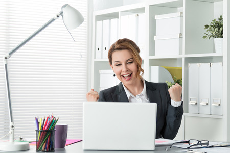Beautiful happy business woman celebrating with arms up Stock Photo