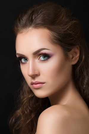Close-up beauty portrait of young pretty brunette model with fashion smokey eyes make-up. Stock Photo