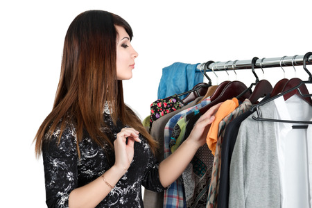 HESITATE: Beautiful young woman near rack with clothes choosing what to take. Nothing to wear, shopping and sale  concept
