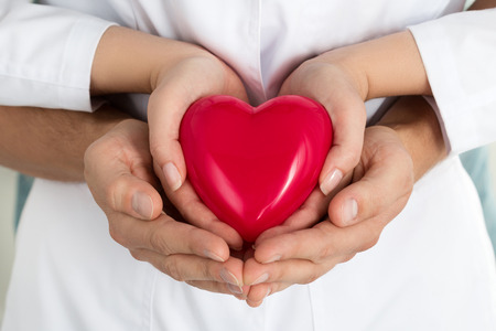 Womans and mans hands holding red heart together. Love, assistance and healthcare concept Stockfoto