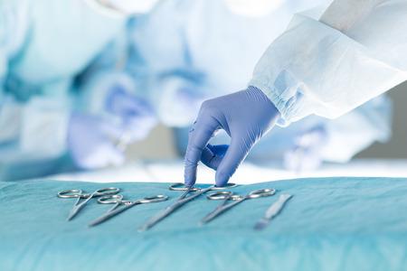 quirurgico: Primer plano de la enfermera instrumentista teniendo instrumentos médicos para el funcionamiento con colegas realizando en segundo plano