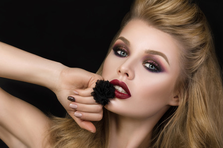 make up eyes: Portrait of beautiful brunet woman with fashion make-up and black ring over dark background