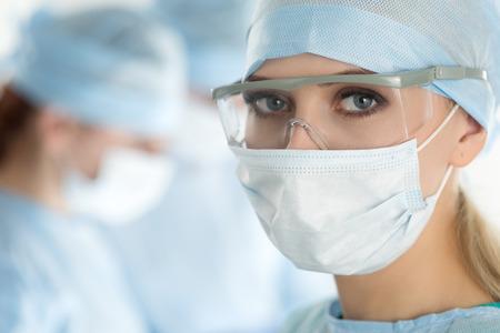 cirujano: Close-up de la mujer cirujano mirando a la cámara con sus colegas realizar en segundo plano en la sala de operación