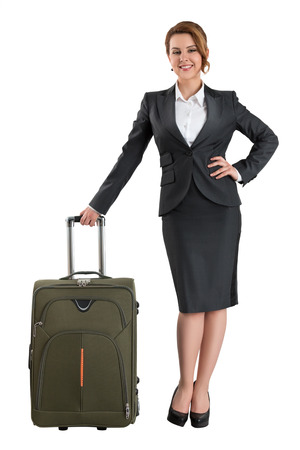 business case: Young beautiful smiling business woman standing with travel suitcase. Business travel and vacation concept. Isolated on white background Stock Photo