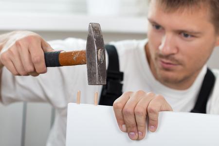 Hombre armar muebles de autoensamblaje en el nuevo hogar de cerca. Bricolaje, hogar y el concepto de movimiento