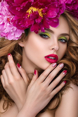 fashion catwalk: Close-up beauty portrait of young pretty girl with flower wreath in her hair wearing bright pink lipstick and touching her lips. Stock Photo