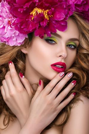 flor violeta: Close-up retrato de la belleza de la muchacha bonita joven con corona de flores en el pelo que llevaba rosa brillante l�piz de labios y tocar sus labios.