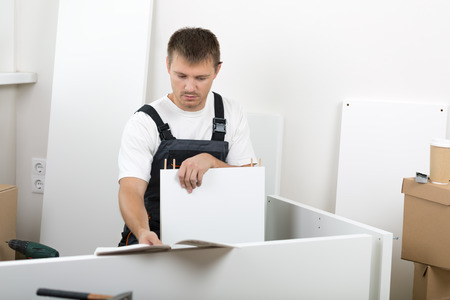 furniture detail: Frustrated man dressed in workers overall reading instruction and putting together self assembly furniture.  Stock Photo