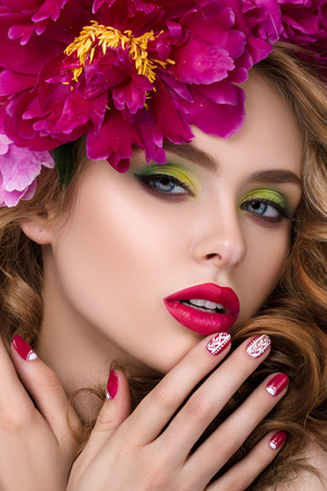 nice face: Close-up beauty portrait of young pretty girl with flower wreath in her hair wearing bright pink lipstick and touching her lips. Stock Photo