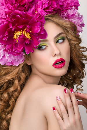 green lipstick: Close-up beauty portrait of young pretty surprised girl with flower wreath wearing bright pink lipstick, touching her lips. Bright modern summer makeup. Beauty, spa, manicure and skincare concept
