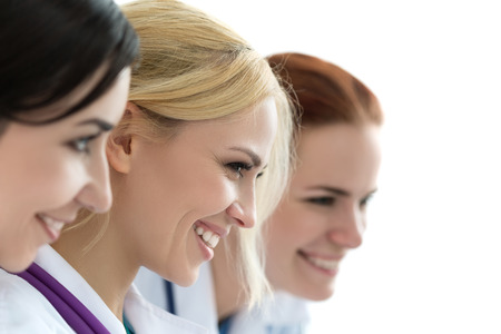 doctors smiling: Three female doctors looking at monitor and smiling. Medical and healthcare concept Stock Photo