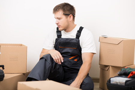 knowing: Frustrated man sitting between brown carton boxes after relocation not knowing what to do. DIY, new home and moving concept Stock Photo