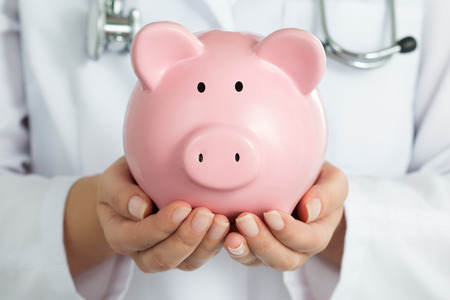 medics: Female Doctor Holding Piggy Bank. Doctors hands close-up. Medical insurance and health care concept.