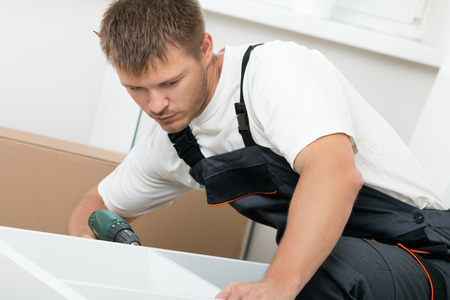 self assembly: Man putting together self assembly furniture in new home. DIY, new home and moving concept Stock Photo
