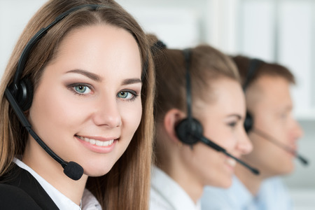 call center office: Portrait of call center worker accompanied by her team. Smiling customer support operator at work. Help and support concept