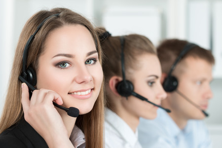 helpdesk: Portrait of call center worker accompanied by her team. Smiling customer support operator at work. Help and support concept