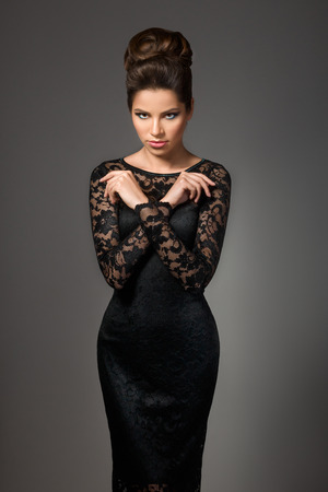 over black: Beautiful young model in black dress with evening makeup and hairdo posing over gray background