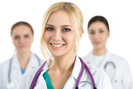 healthcare portrait: Portrait of young blonde female doctor surrounded by medical team, looking at camera and smiling. Healthcare and medicine concept.