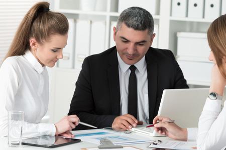 Adult zakenman overleg met zijn jonge vrouwelijke collega tijdens zakelijke bijeenkomst. Partners bespreking van documenten en ideeën Stockfoto