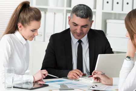 Adult businessman consulting his young female colleague during business meeting. Partners discussing documents and ideas