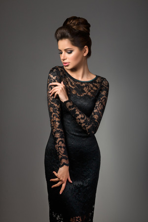 beautiful dress: Beautiful young model in black dress with evening makeup and hairdo posing over gray background