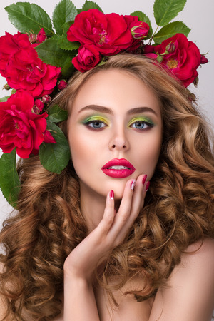 spa treatments: Close-up beauty portrait of young pretty girl with flower wreath in her hair wearing bright pink lipstick, touching her lips. Bright modern summer makeup. Beauty, spa, manicure and skincare concept Stock Photo