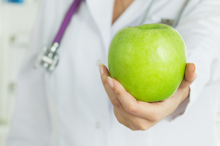 dietology: Female doctors hand offering fresh green apple. Healthy life, wholesome and healthcare concept. Copy space