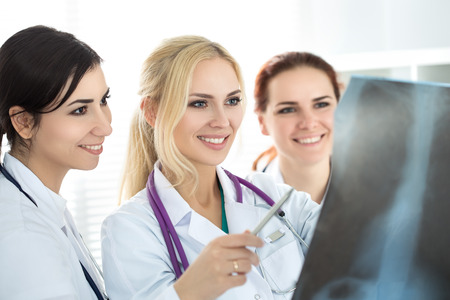 work team: Three smiling female medicine doctor looking at x-ray picture. Healthcare and medicine concept.