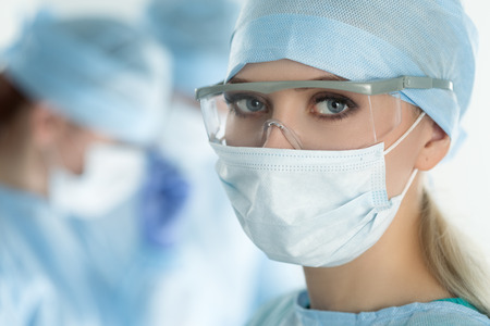 surgeon mask: Close-up of surgeon woman looking at camera with colleagues performing in background in operation room