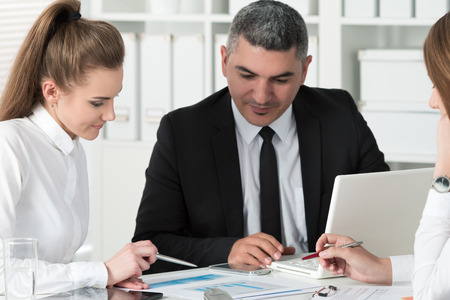 consulting business: Adult businessman consulting his young female colleague during business meeting. Partners discussing documents and ideas
