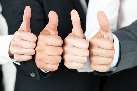 Business team pointing up their thumbs. of different business people pointing up. Concept of success and teamwork. Standard-Bild